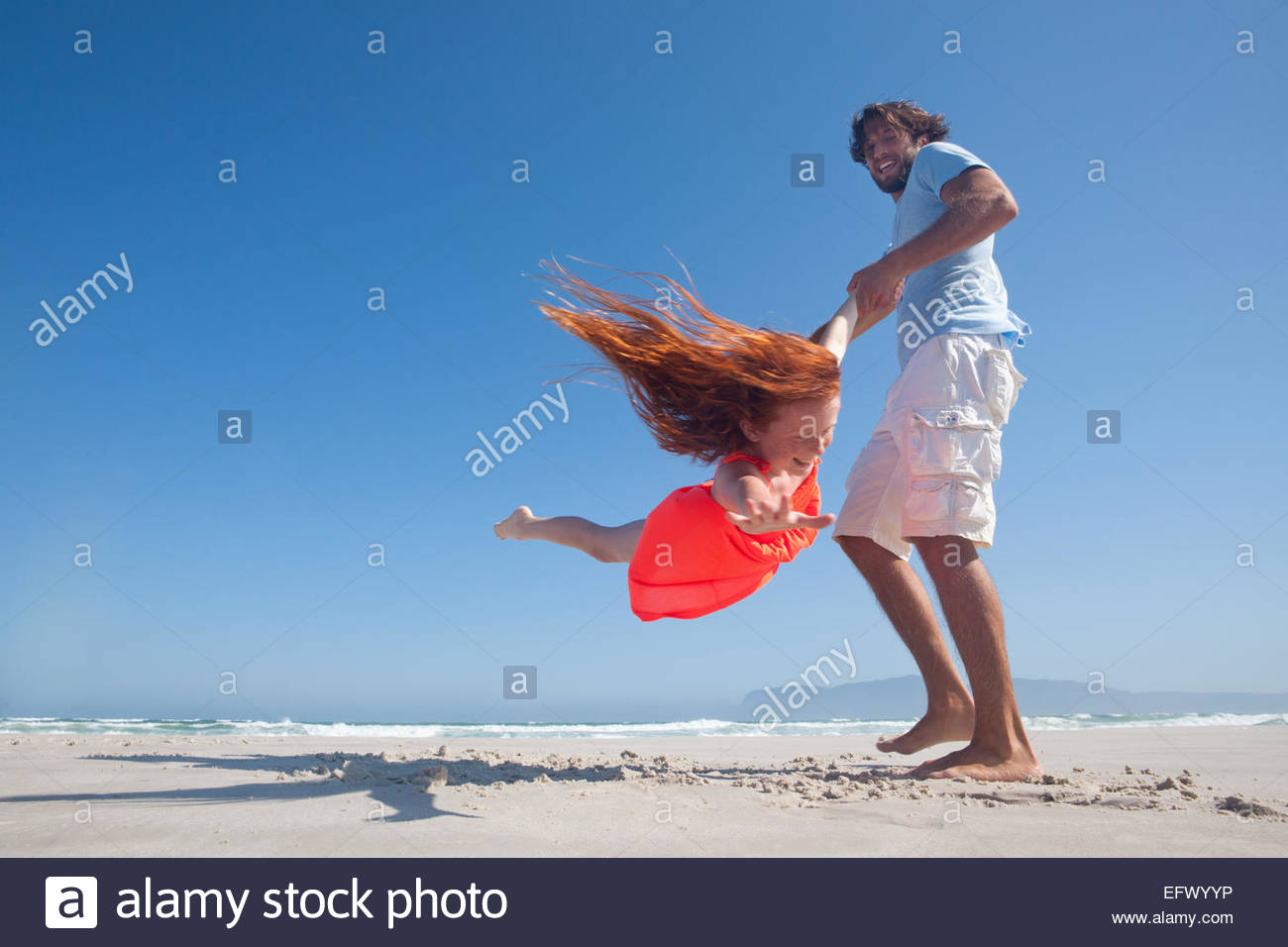 Smiling Father swinging fille jouant autour sur sunny beach Photo Stock