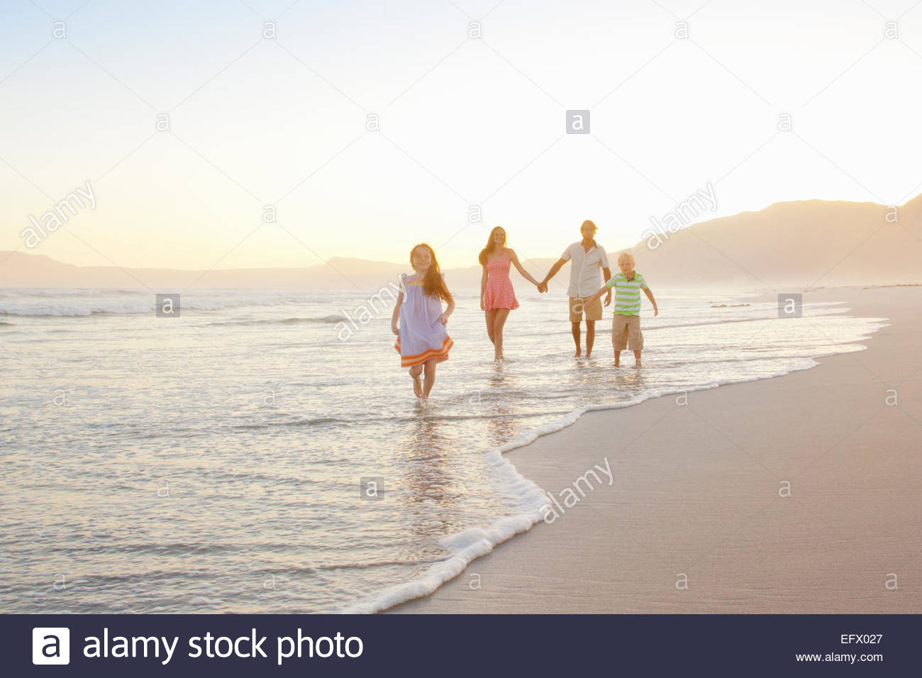 Happy Family holding hands on sunny beach Photo Stock