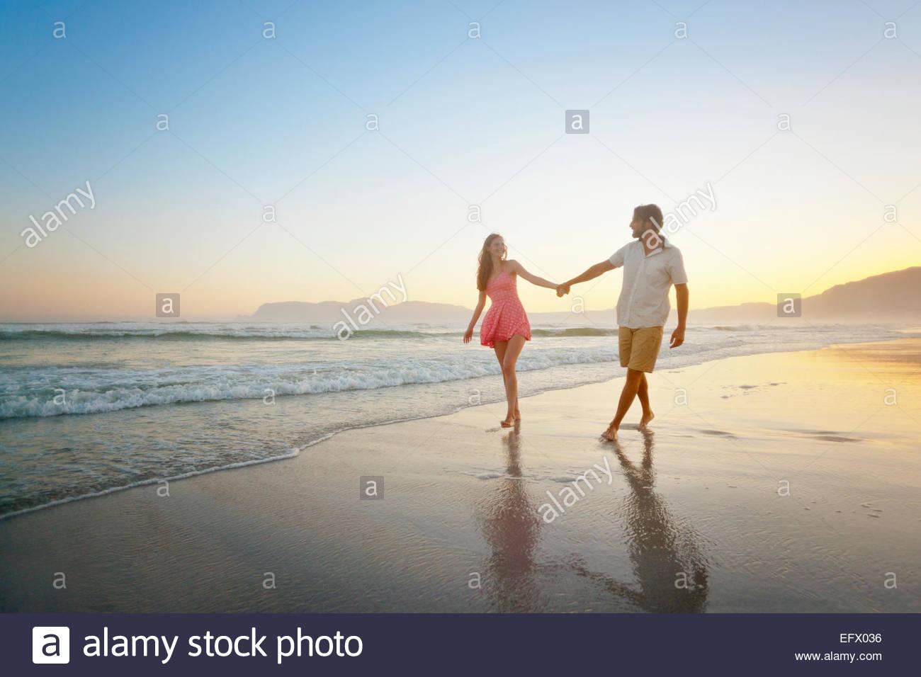 Couple, se tenir la main, marcher le long de sunny beach Photo Stock