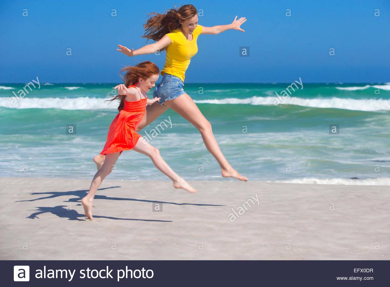 Mère et fille sautant, avec les bras tendus, on sunny beach Photo Stock