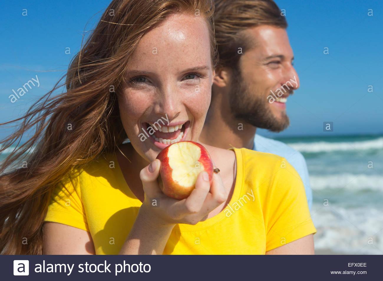 Smiling couple sur la plage ensoleillée, avec woman holding an apple avec une bouchée de c Photo Stock