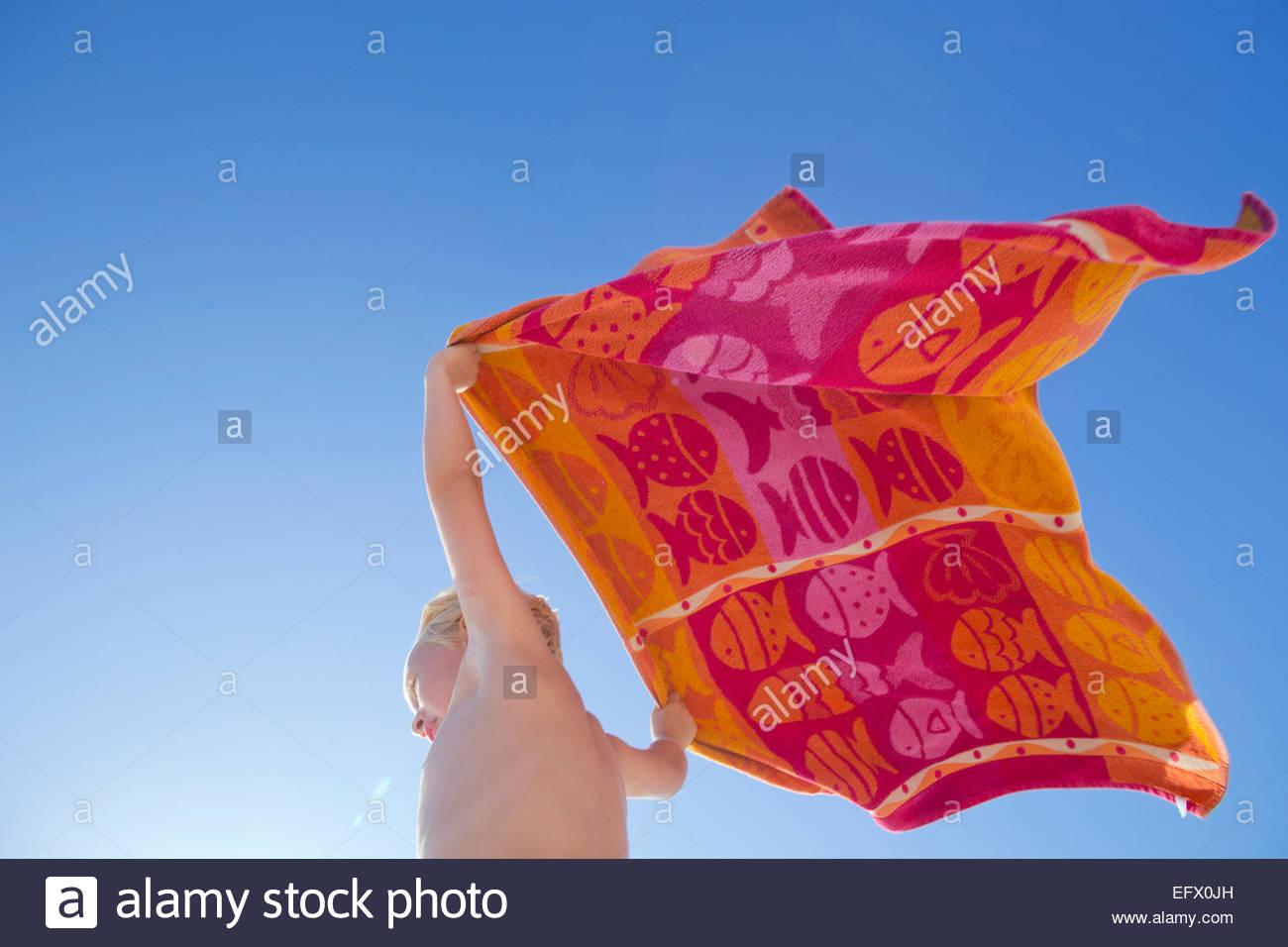 Portrait of boy holding towel au-dessus de la tête dans le vent sur sunny beach Photo Stock
