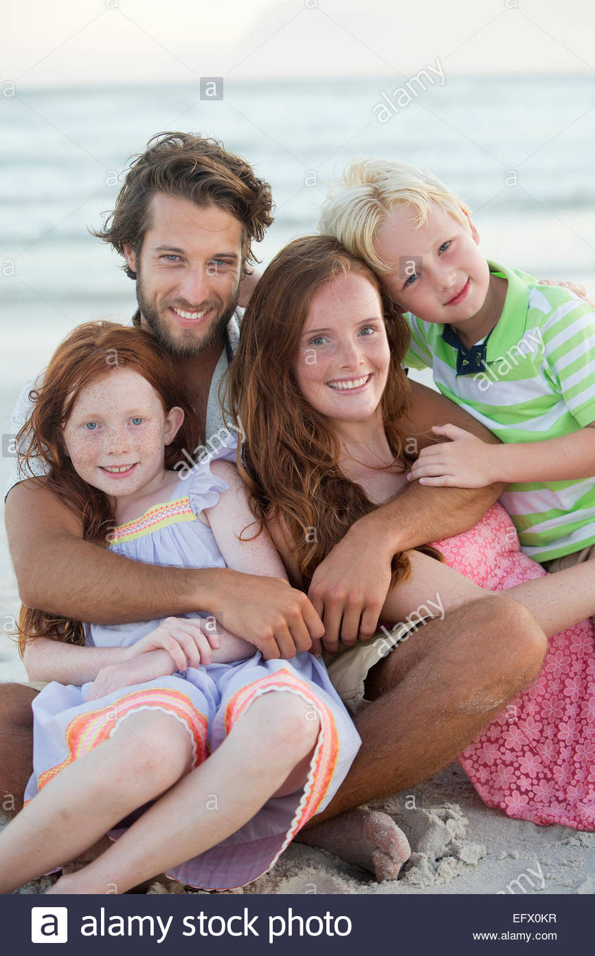 Portrait de famille, smiling at camera, embracing on sunny beach Photo Stock