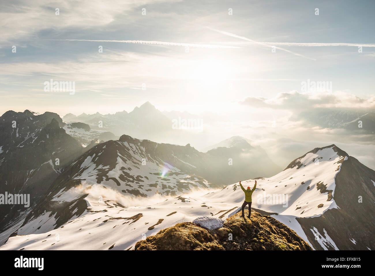 Jeune homme trekker mountain avec bras levés en Alpes bavaroises, Oberstdorf, Bavière, Allemagne Photo Stock