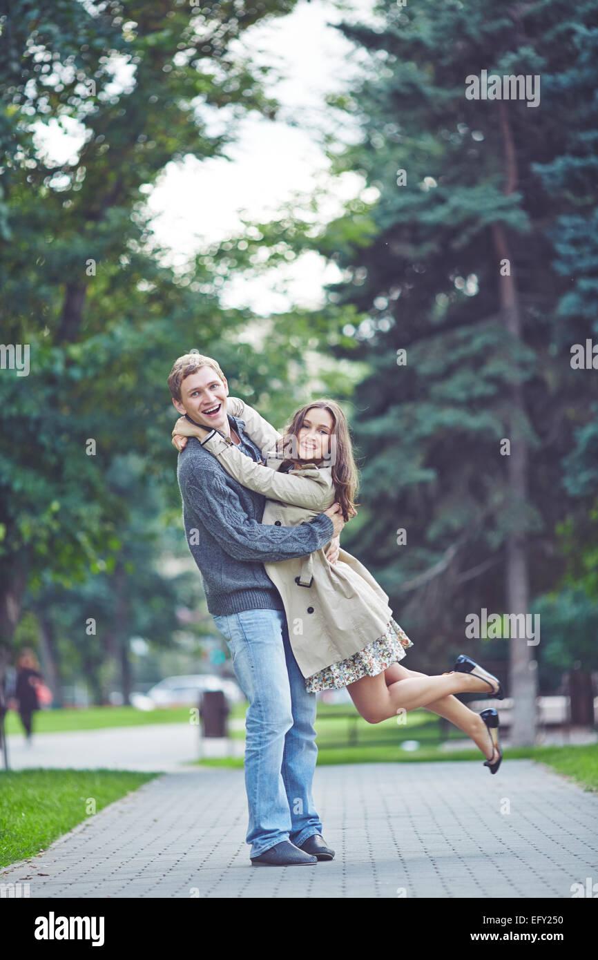 Heureux guy tenant sa petite amie extatique dans park Photo Stock