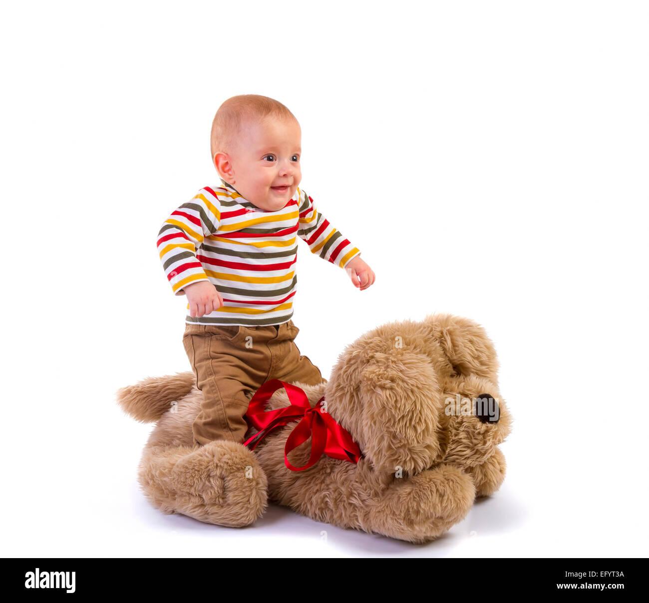 Baby boy saute sur plush dog sur fond blanc Photo Stock