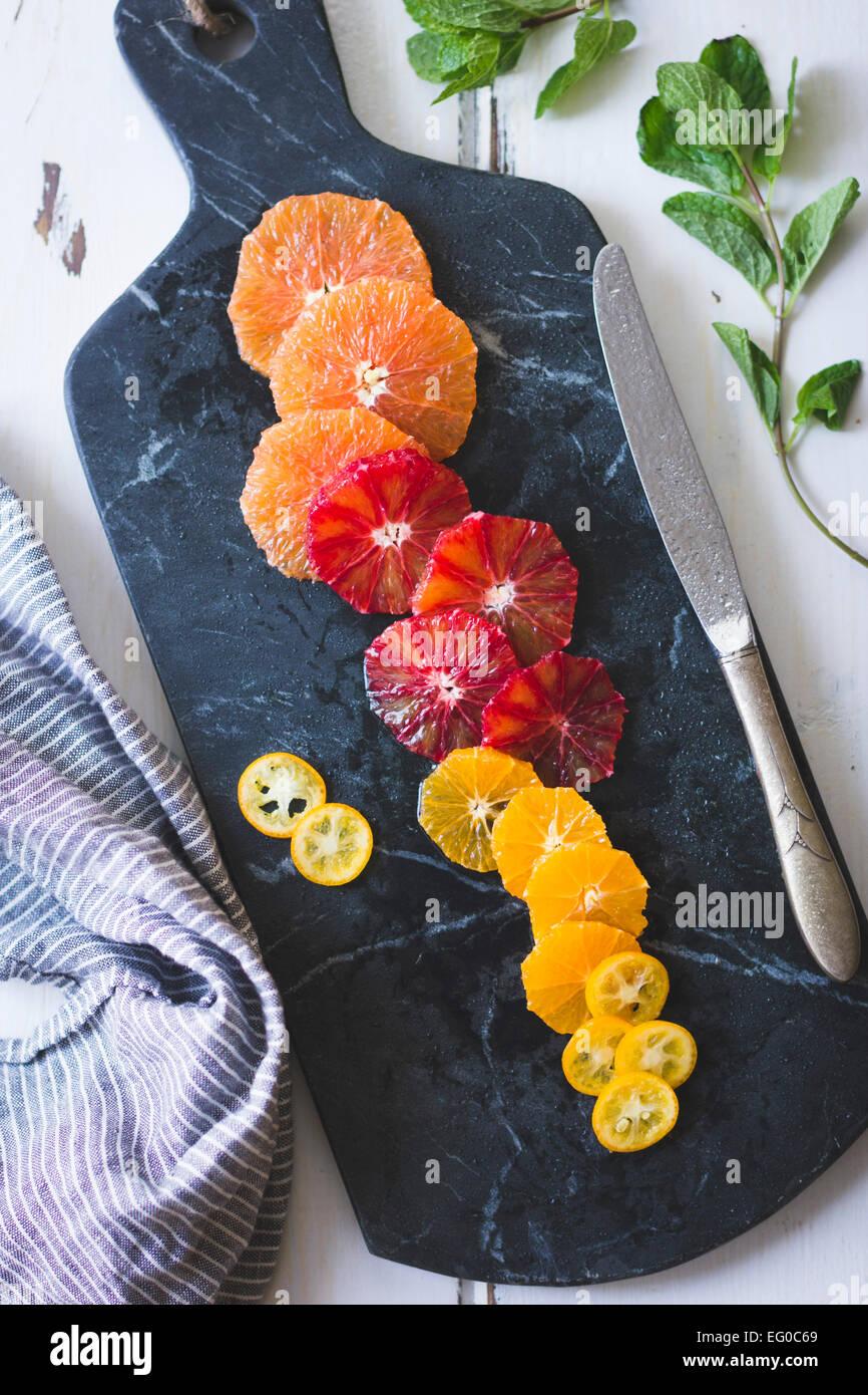 Agrumes sur une planche à découper en marbre. Photo Stock