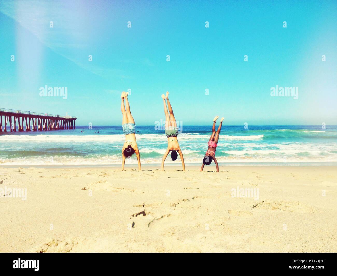 Mère, père et fille doing handstand on beach Banque D'Images