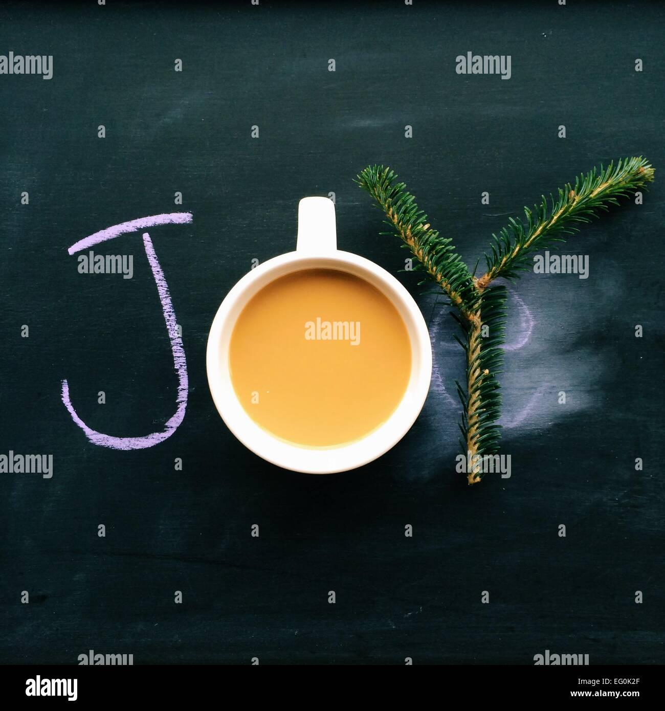 Mot joie écrit sur tableau noir avec du café et de la direction générale des sapins Photo Stock
