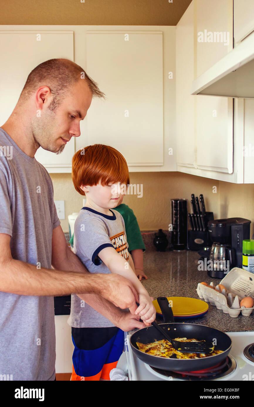 Deux garçons aident leur père faire des œufs pour le petit déjeuner Photo Stock