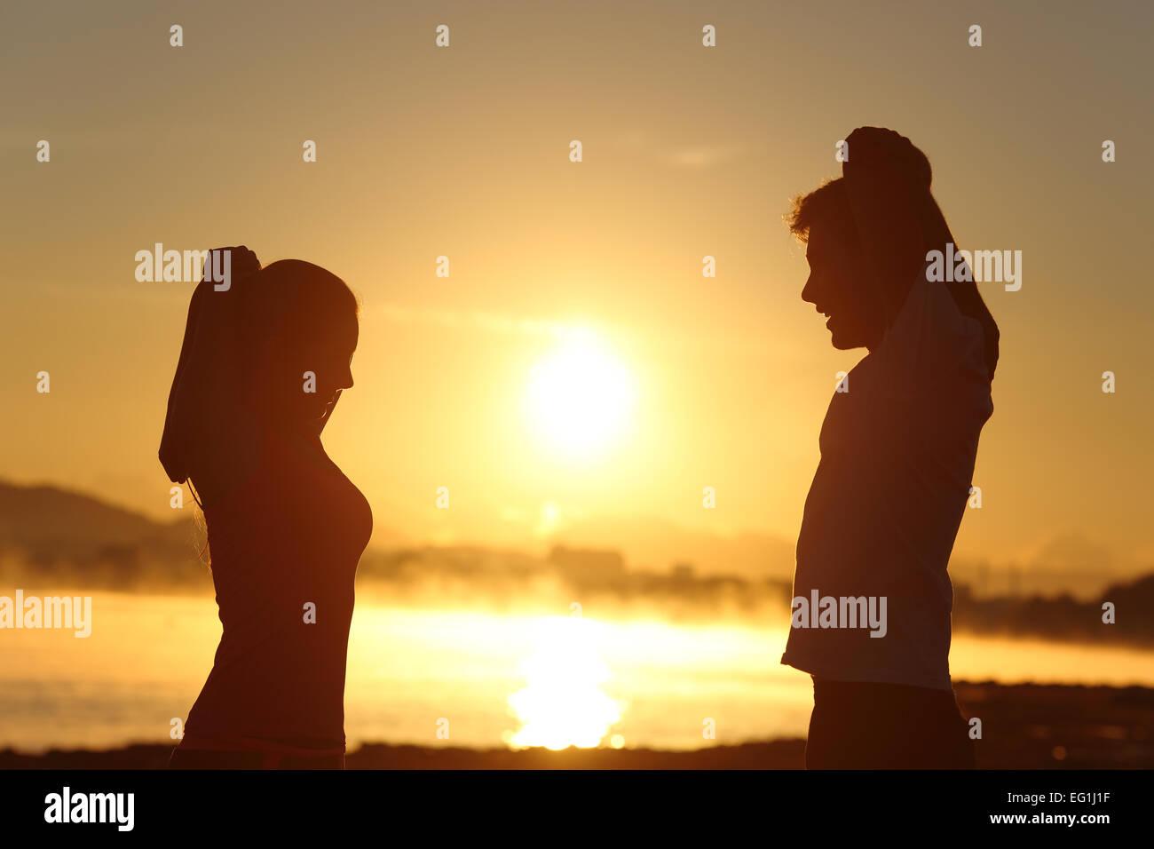 Silhouette d'un couple stretching remise en forme au lever du soleil avec le soleil en arrière-plan Photo Stock
