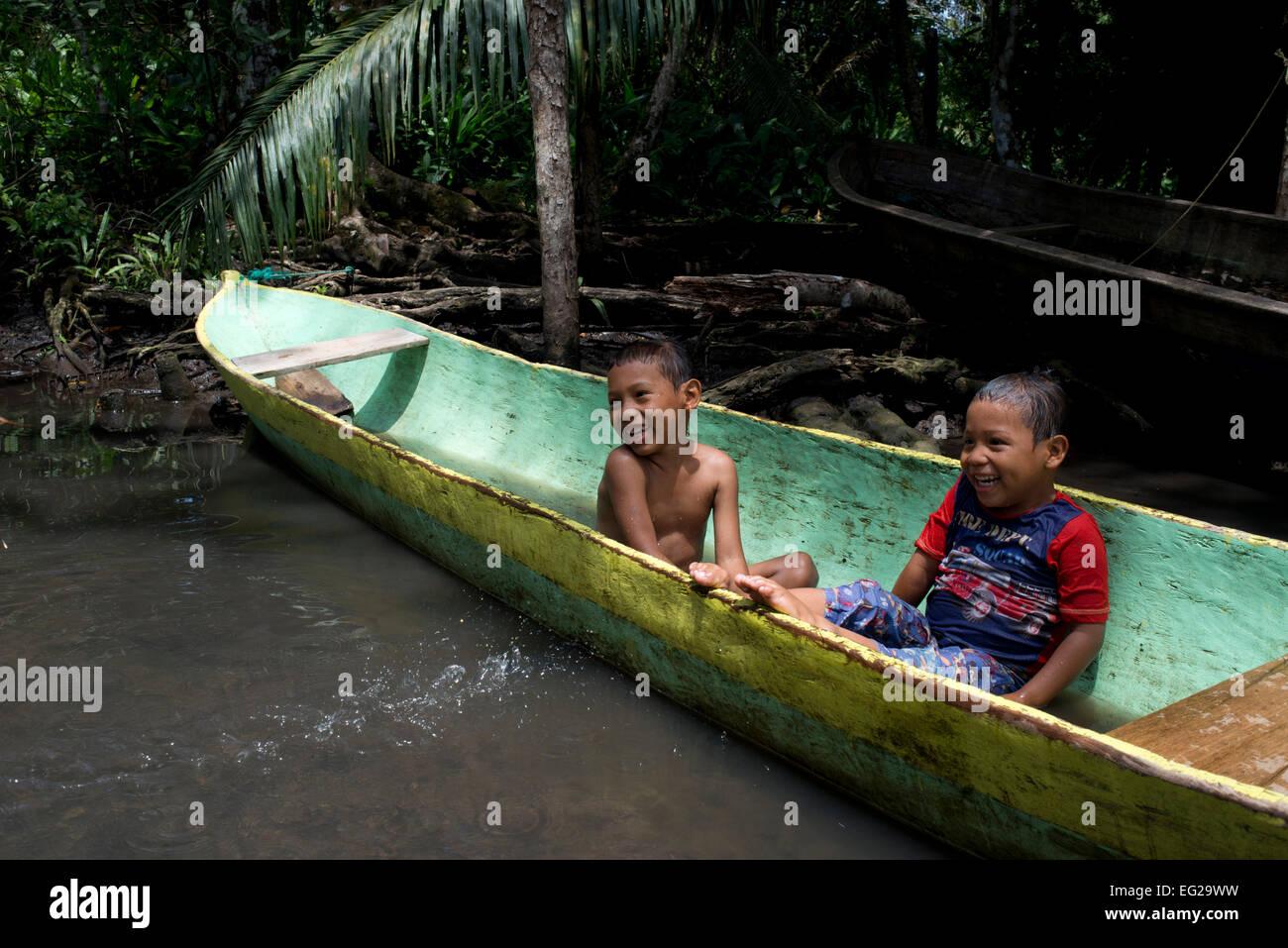 Les enfants jouent dans l'un des bateaux locaux utilisés par les indiens Ngobe comme principale forme de transport, à l'abri sous un maigre fortune- Banque D'Images