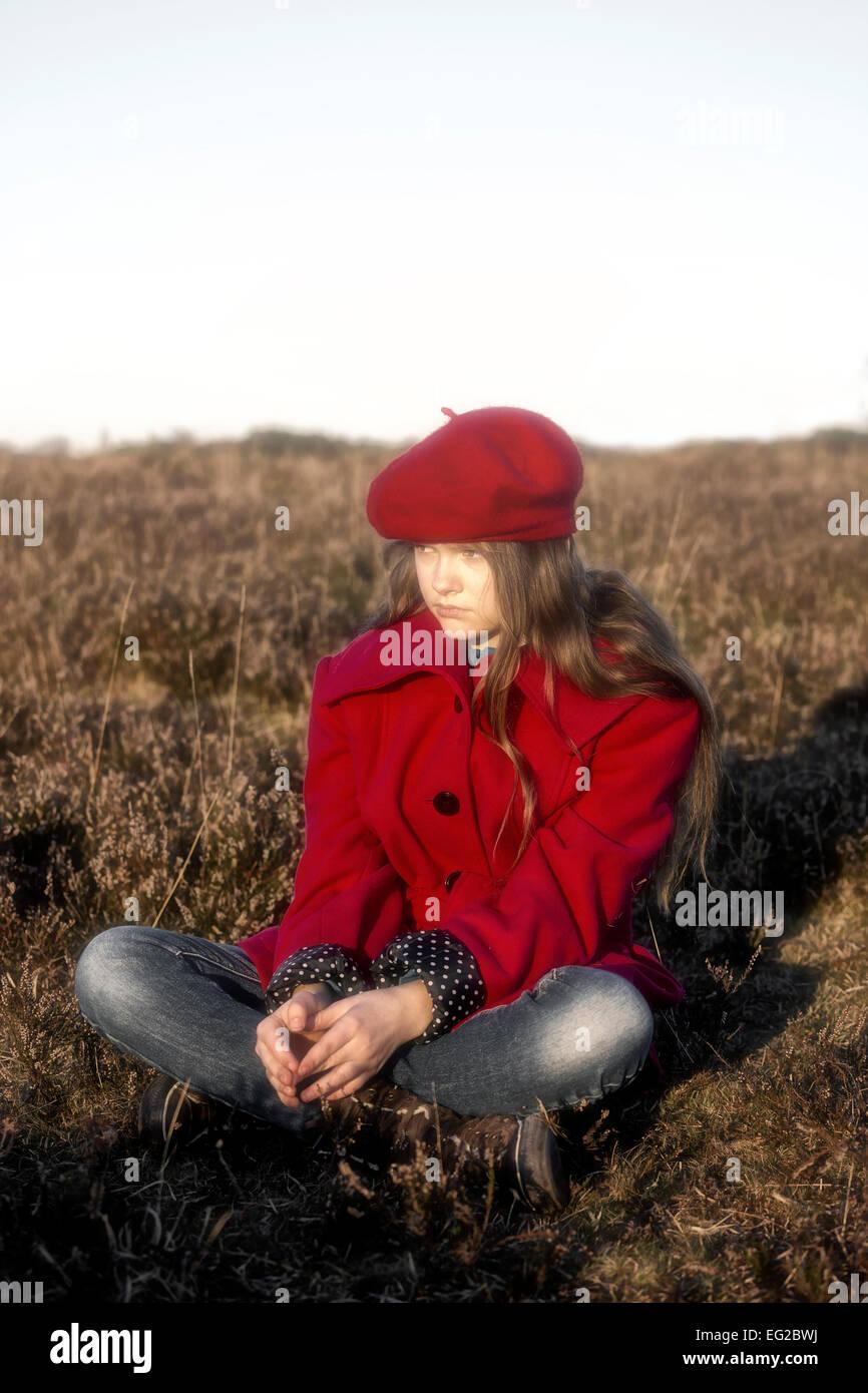 Une fille dans un manteau rouge est assis sur une colline Photo Stock