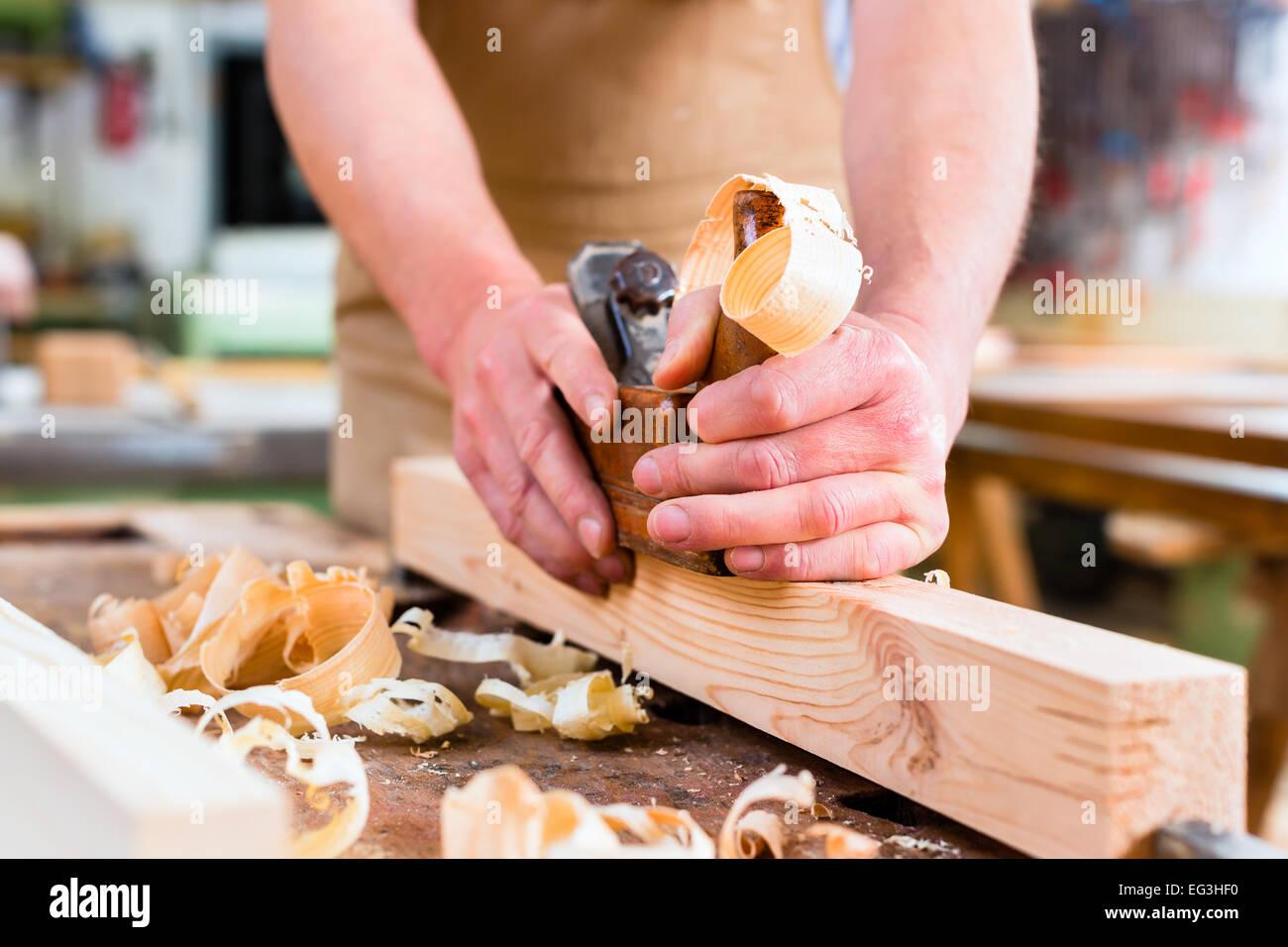 Menuisier travaillant avec un bois de charpente sur la pièce dans son atelier de menuiserie ou Banque D'Images