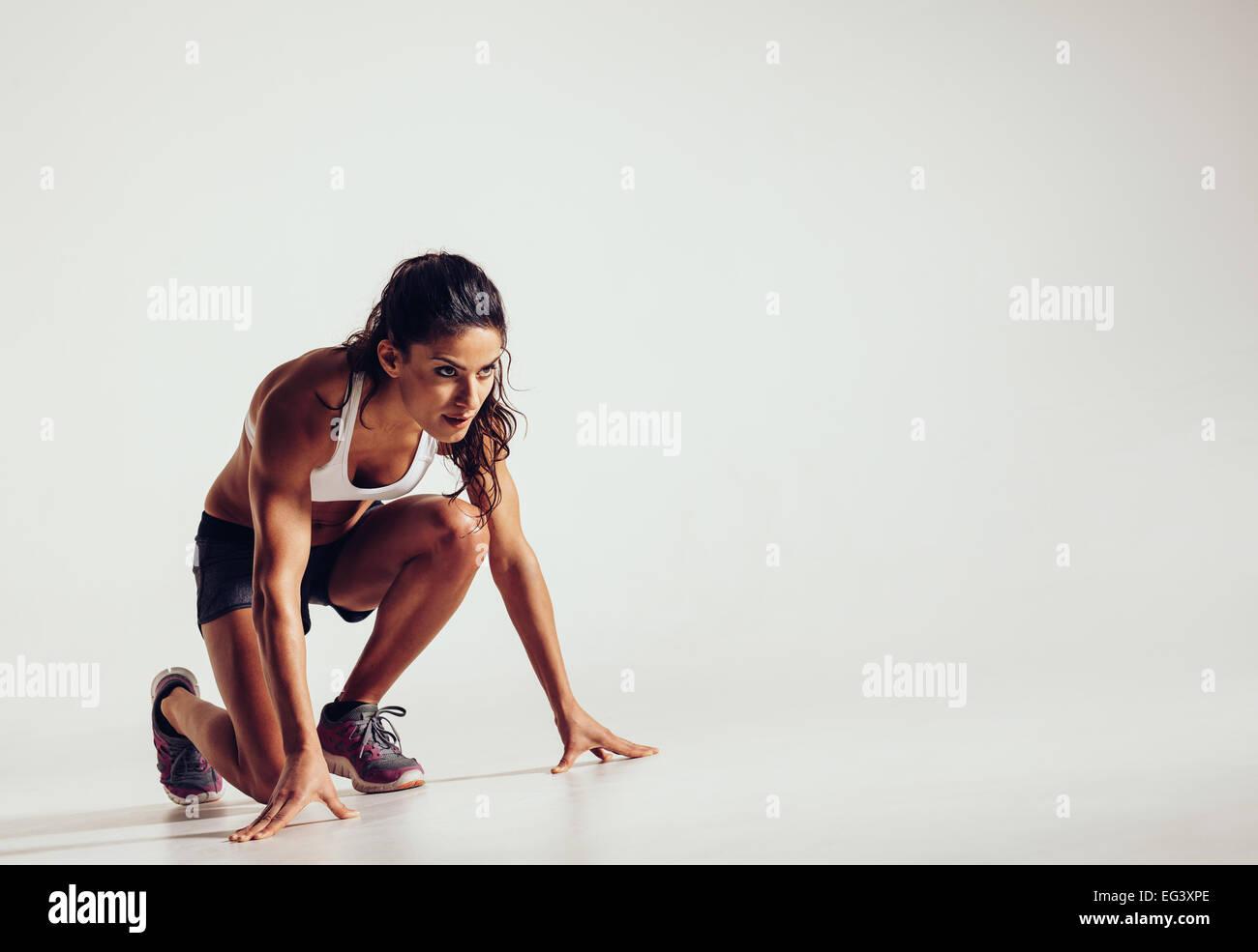 Athlète féminin en position prêt à fonctionner sur fond gris. Jeune femme déterminée Photo Stock