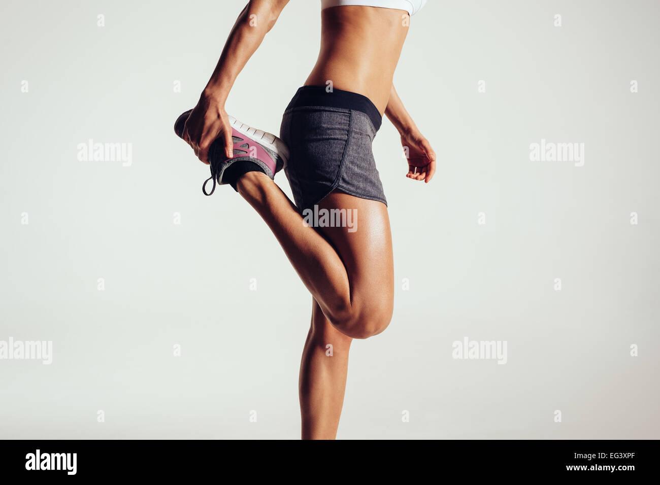 Portrait d'une femme de remise en forme s'étendant ses jambes contre fond gris. Monter coureuse faisant Photo Stock