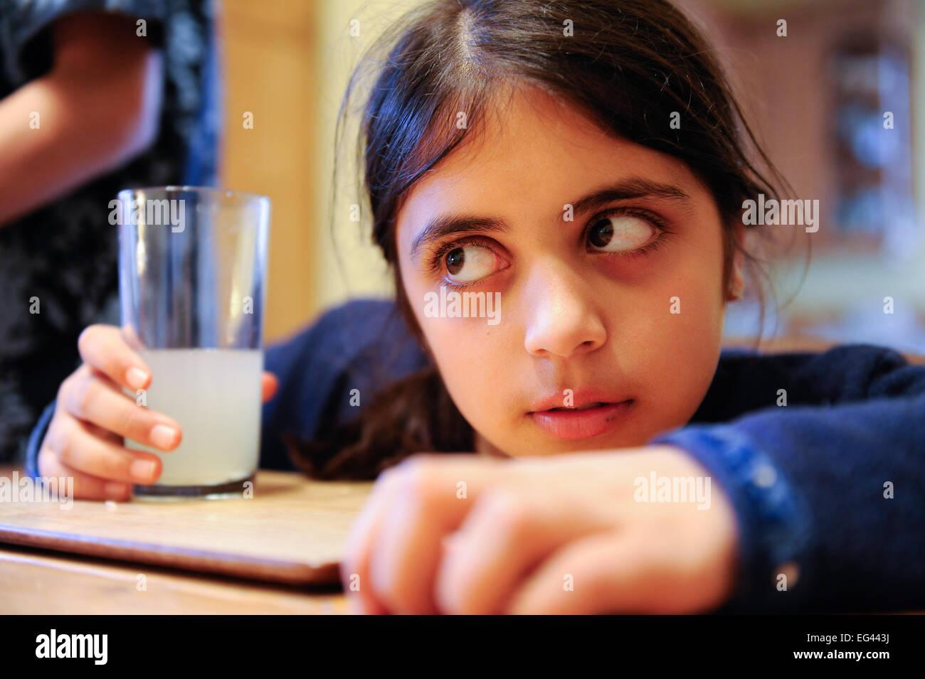 Jeune fille tenant un verre de limonade dans un verre croit profondément à ce qui se passe ailleurs dans Photo Stock