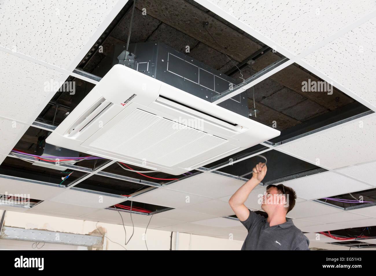 Electricien installation climatisation faux plafond dans l'unité Photo Stock