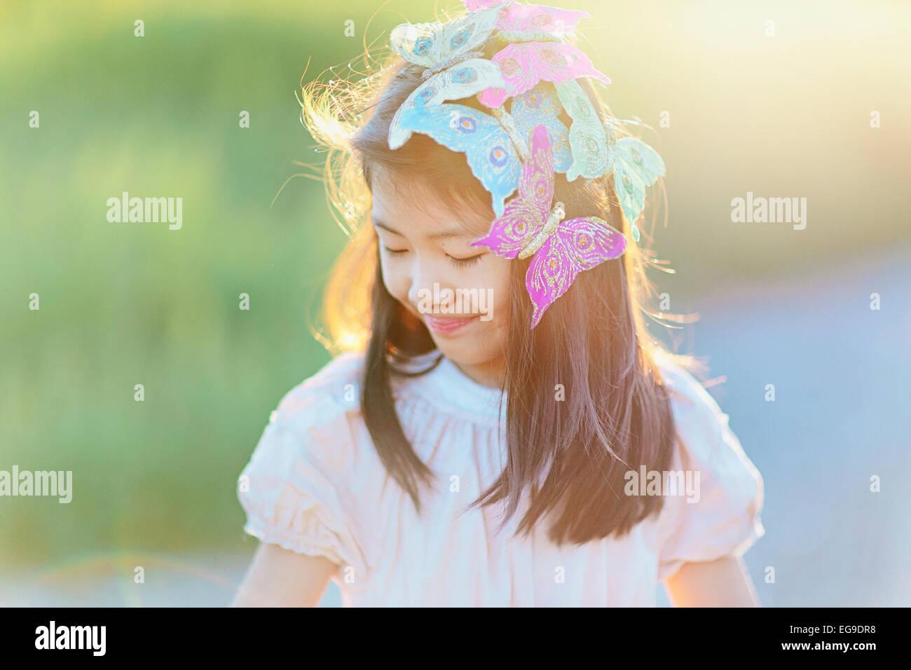Girl (8-9) avec les papillons dans les cheveux Photo Stock