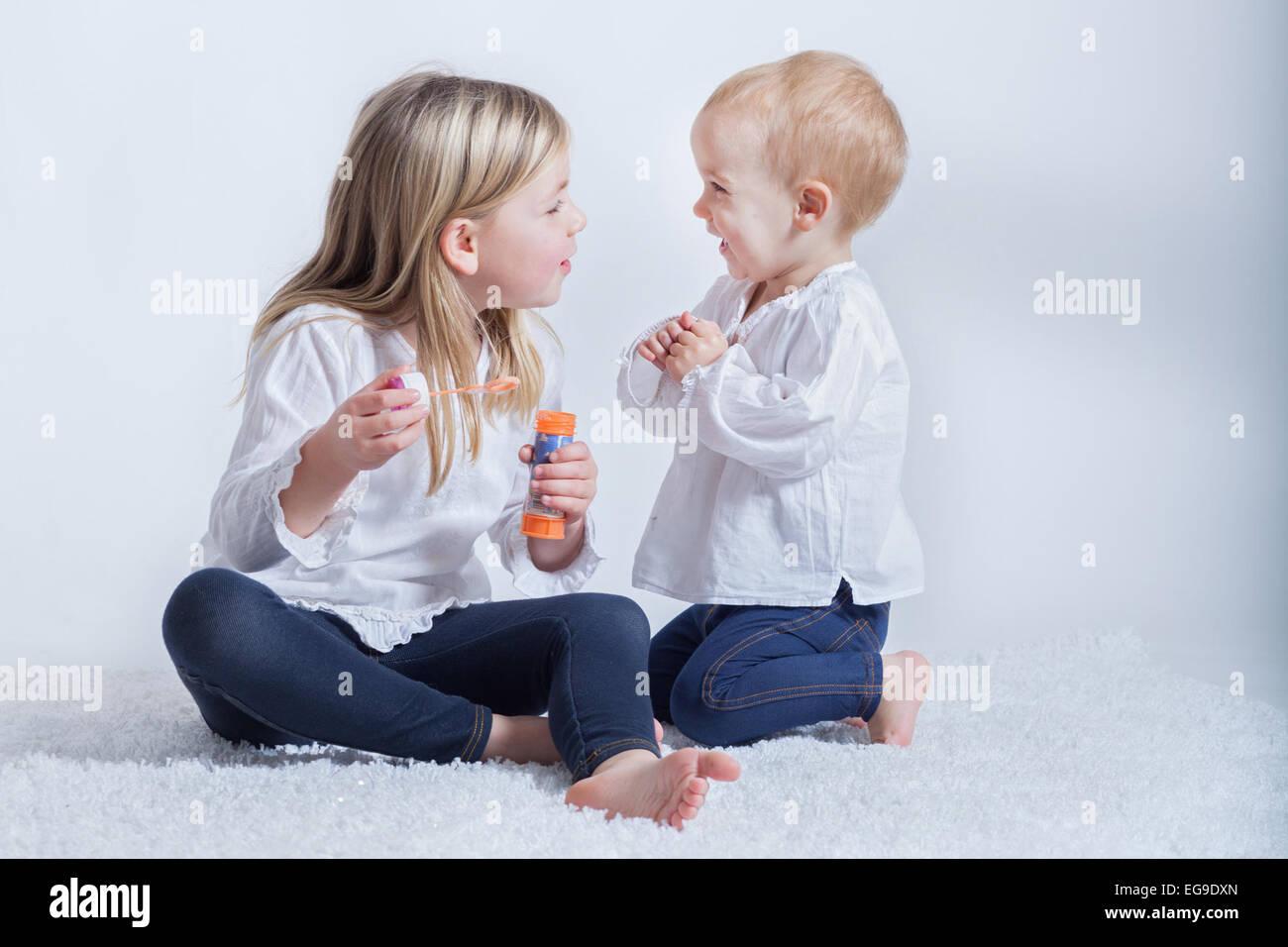Frères et sœurs (2-3, 6-7) à jouer avec bubble wand Photo Stock