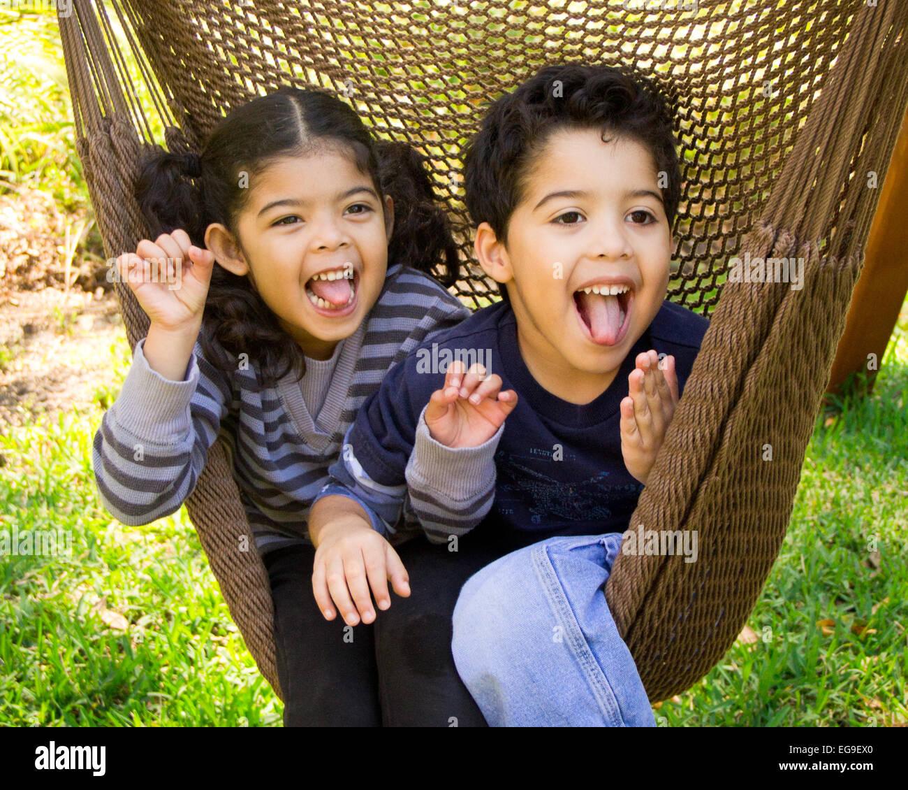 Frère et soeur assis dans un hamac pulling funny faces Photo Stock