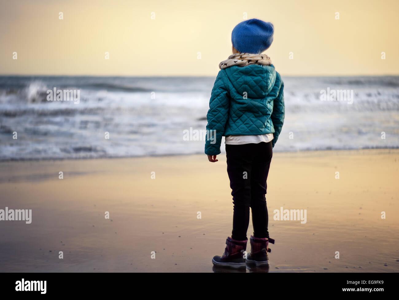 Girl (2-3) à la recherche de plage au coucher du soleil Photo Stock