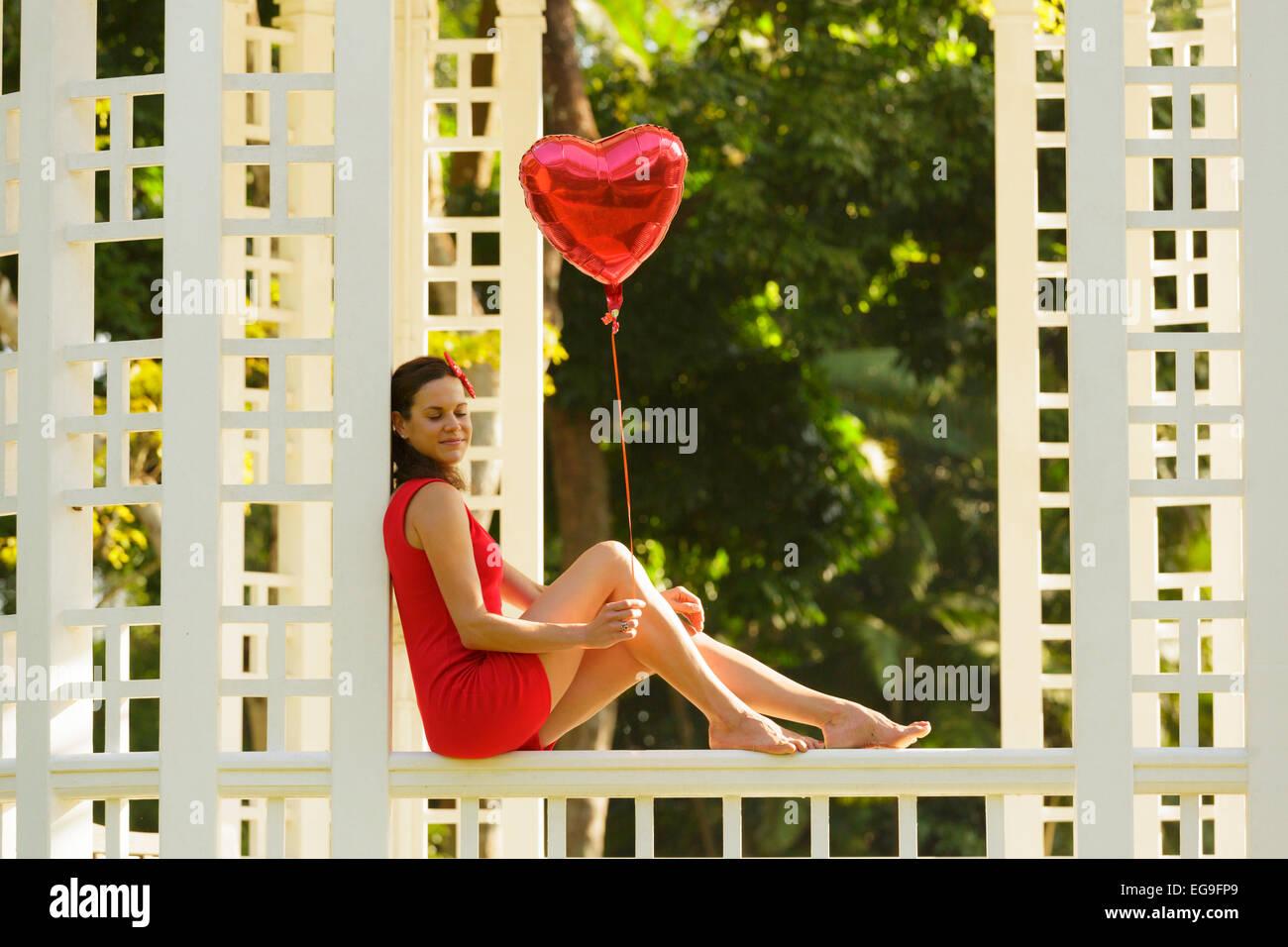 Femme avec ballon en forme de coeur rouge assis sur banc de parc Photo Stock