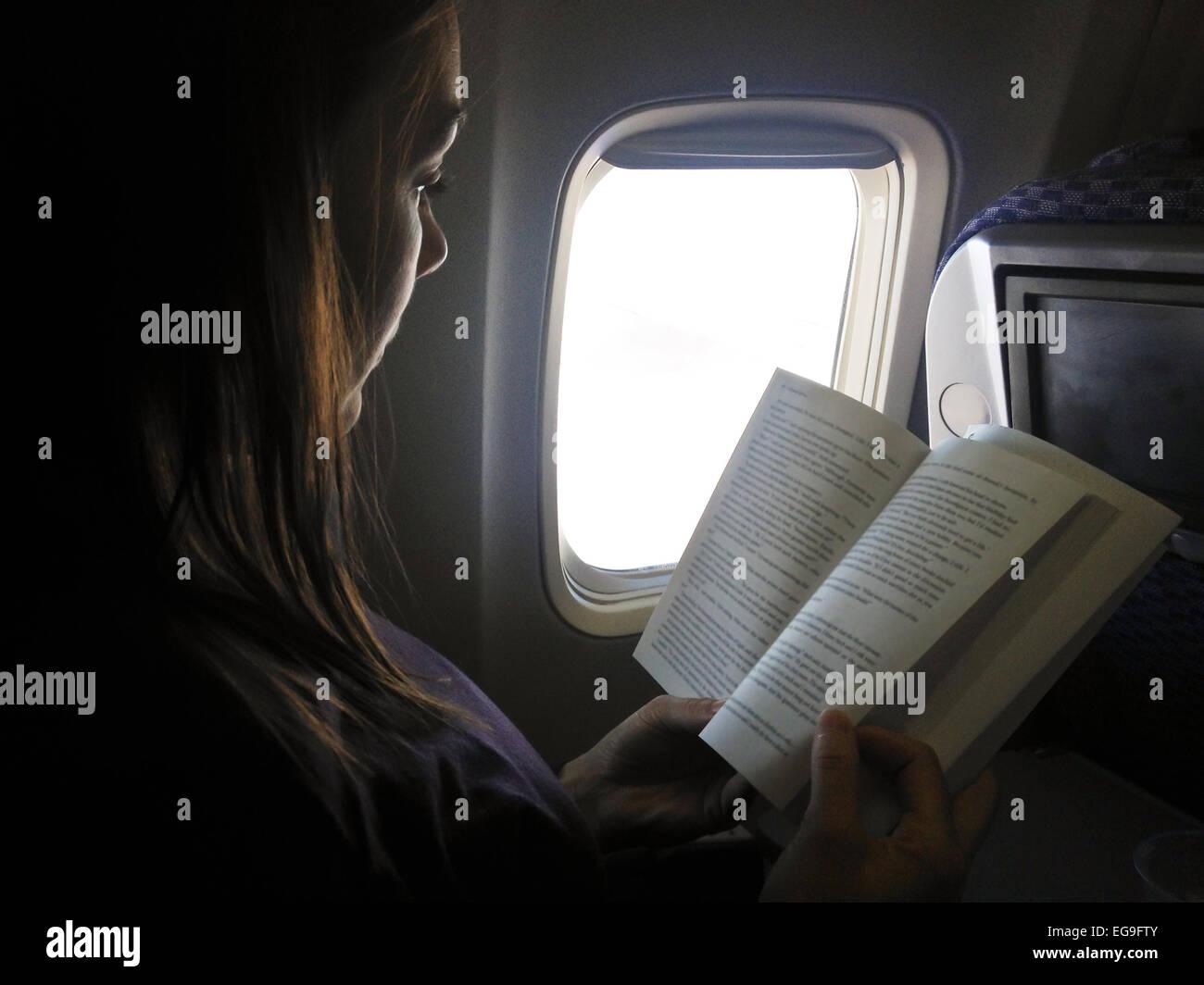 Woman reading on flight Photo Stock