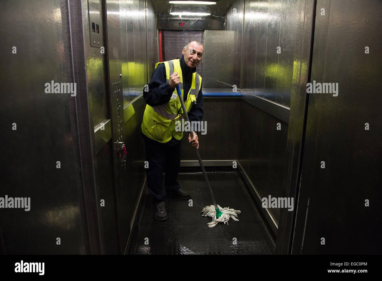 L'homme la serpillière d'un ascenseur ou l'ascenseur dans un immeuble d'appartements à Photo Stock