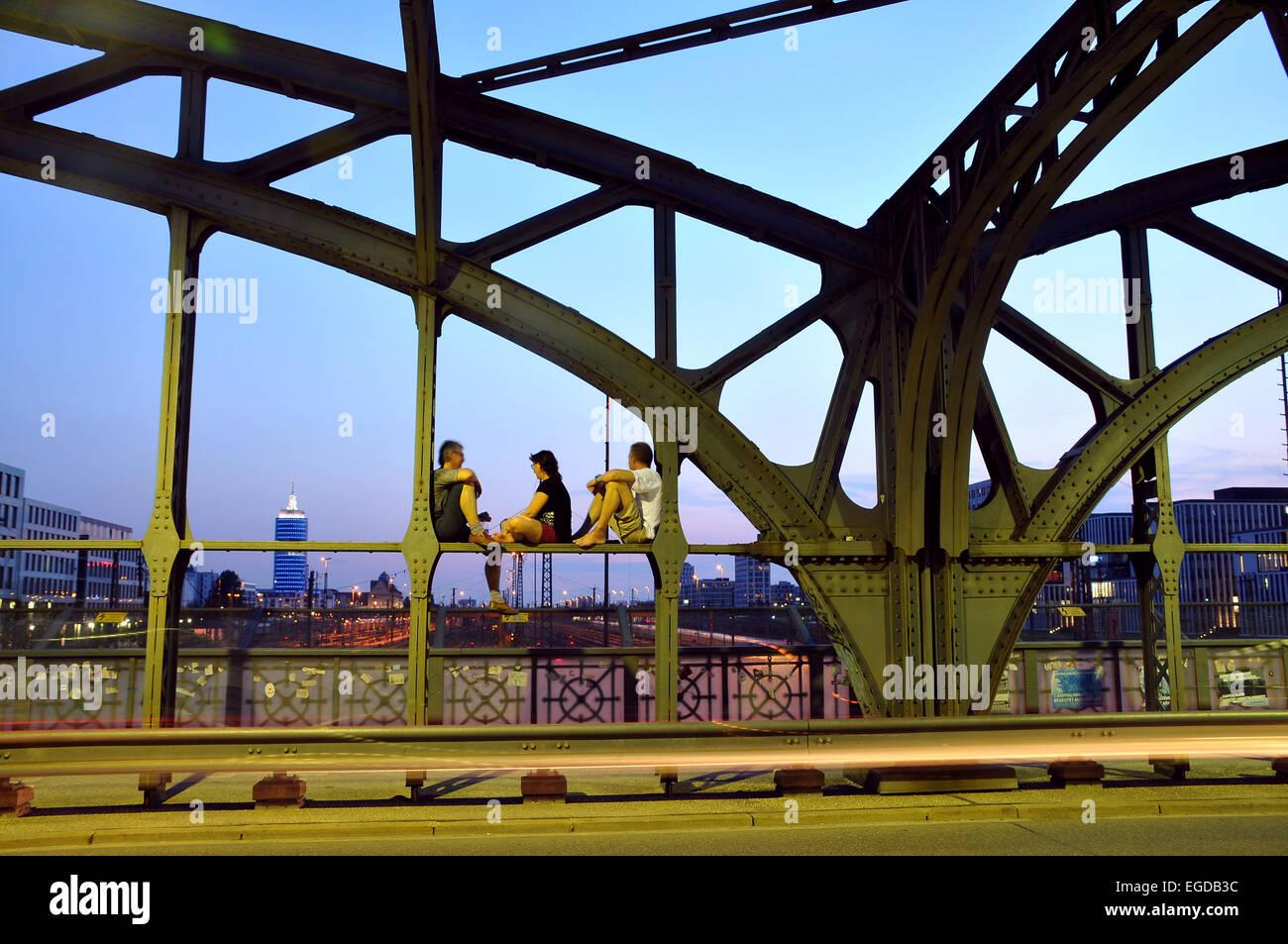 Des gens assis sur le pont d'intrus dans la soirée, Munich, Bavière, Allemagne Photo Stock