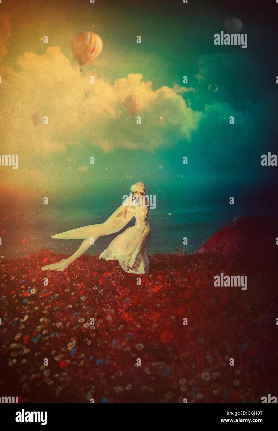 Jeune femme en robe blanche dansant sur la falaise Photo Stock