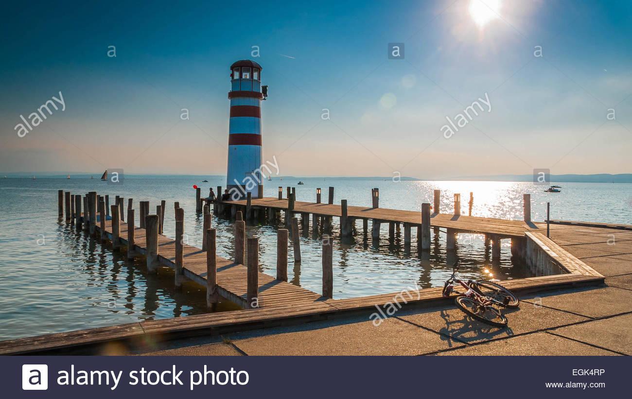 Pier avec phare dans la lumière du soleil Photo Stock
