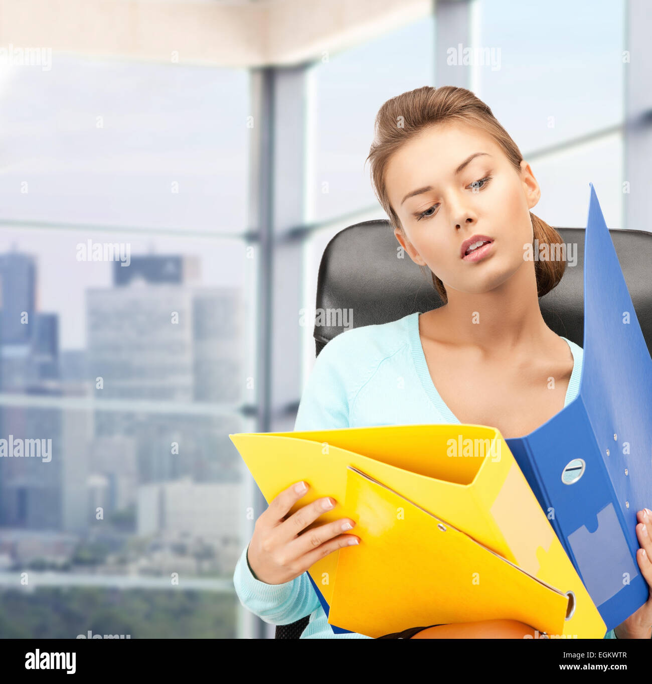 Young businesswoman with folders sitting in chair Banque D'Images