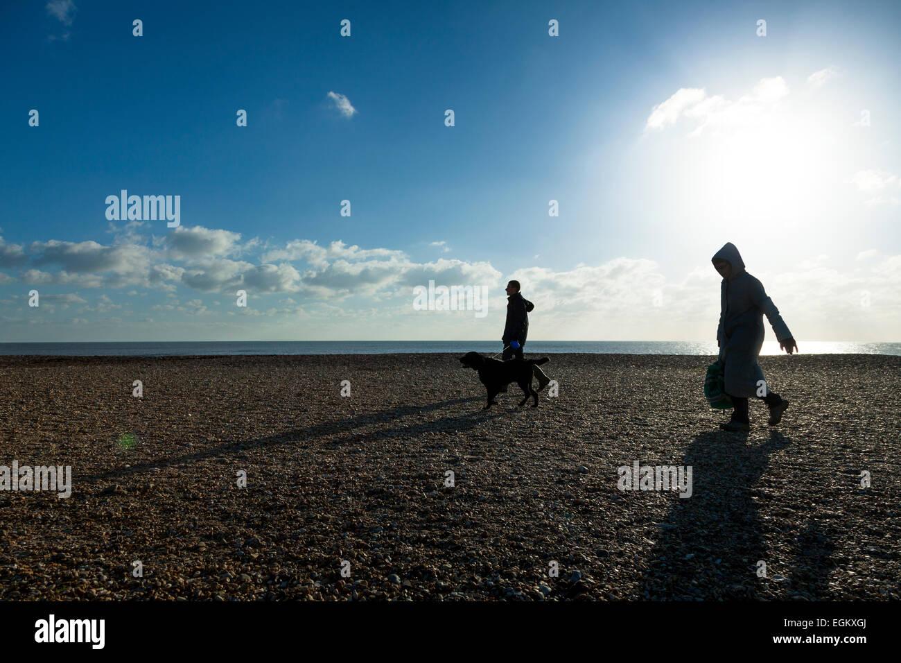 Deux personnes marcher un chien sur une plage de galets sur une journée d'hiver ensoleillée avec sun Photo Stock