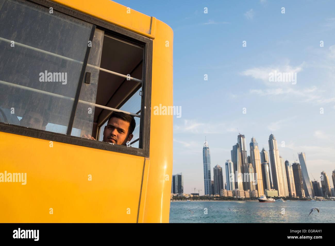 Travailleur de la construction sur le bus pour le logement à la fin de la journée de travail à Dubaï Photo Stock