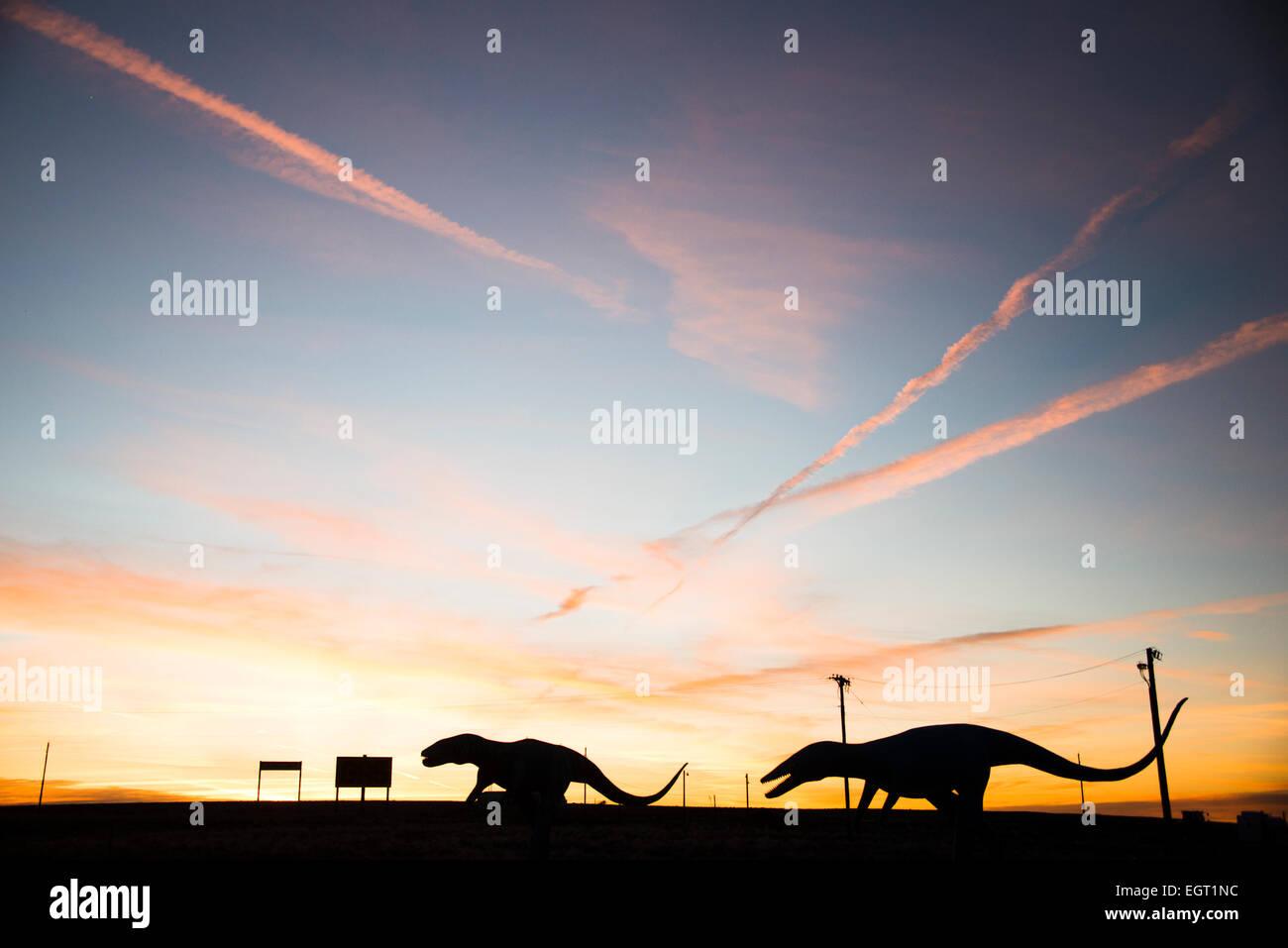 Dinosaure raptor géant chiffres découpé sur le coucher du soleil sur la route 66 près de Holbrook, Arizona USA Banque D'Images
