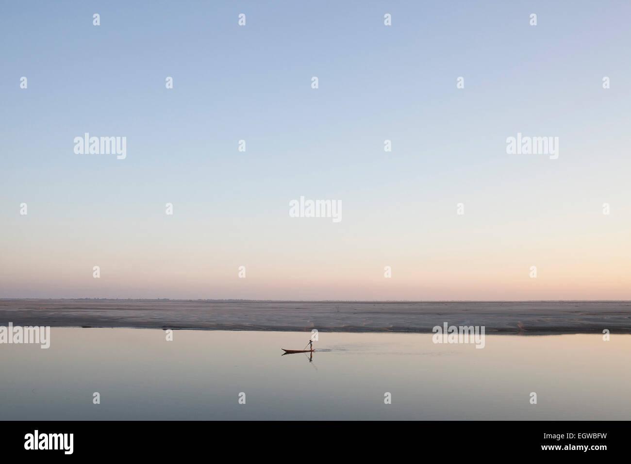 Boatman poling sur Brahmapoutre au coucher du soleil, l'île de Majuli, dans l'Assam, Inde Banque D'Images