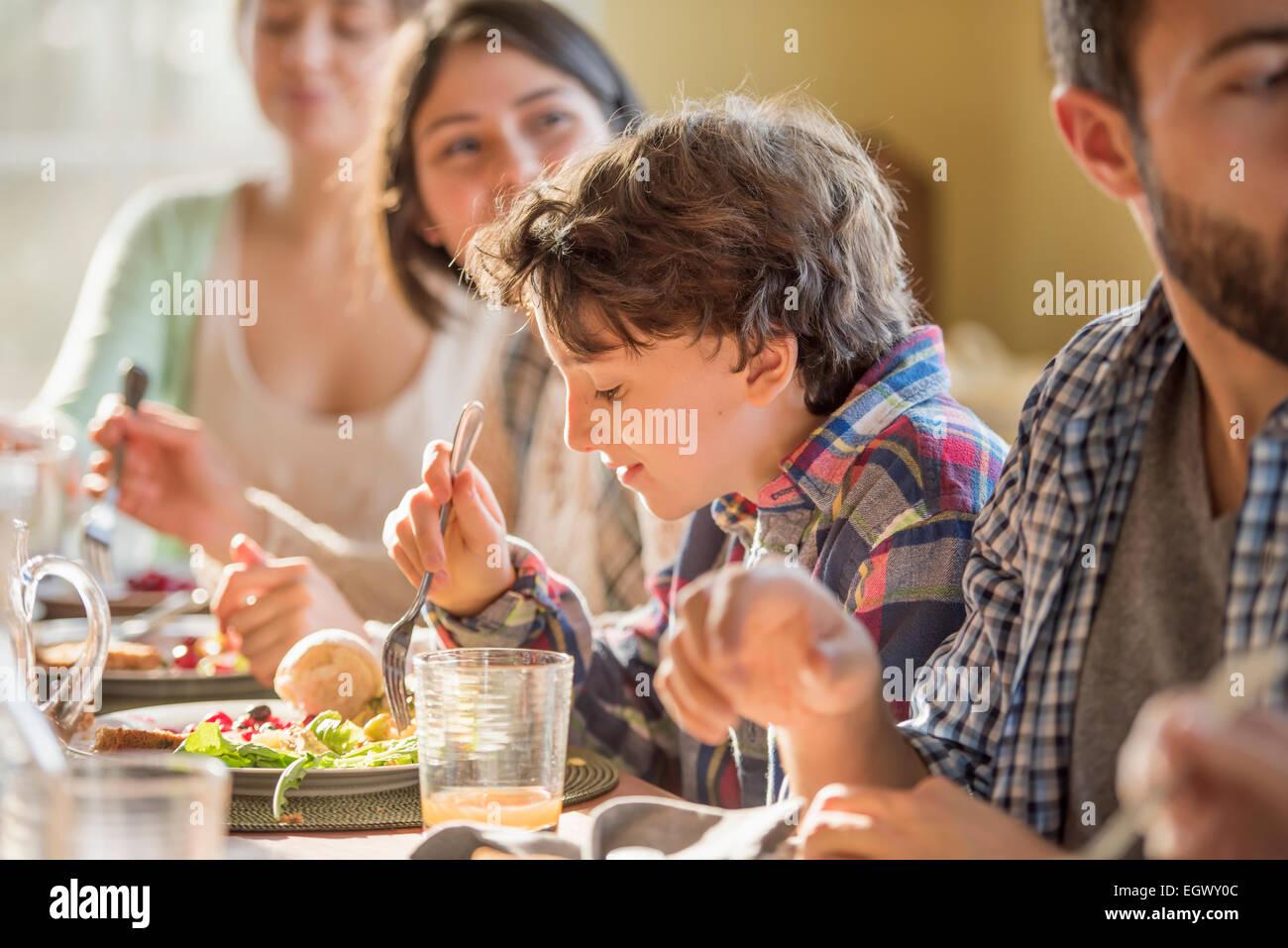 Un groupe de personnes, adultes et enfants, assis autour d'une table pour un repas. Photo Stock