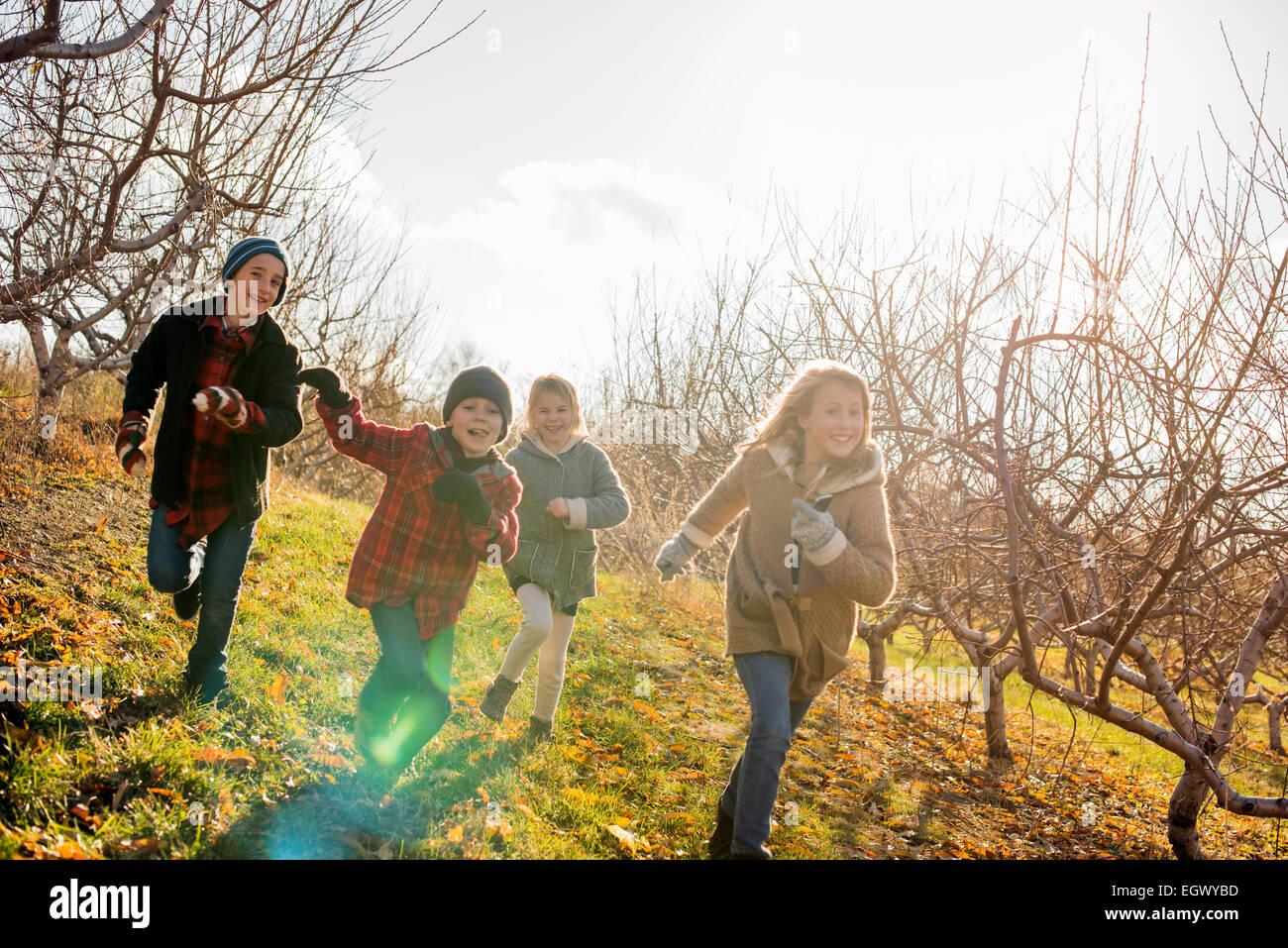 Quatre enfants courir à l'extérieur en hiver Banque D'Images