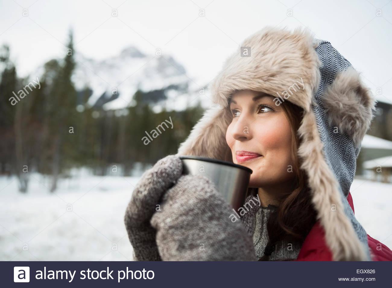 Woman in fur hat de boire un chocolat chaud à l'extérieur Photo Stock