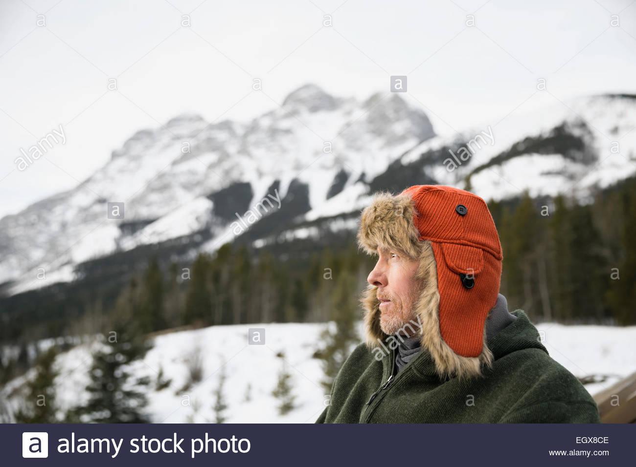 Serious man in fur hat ci-dessous montagnes enneigées Photo Stock