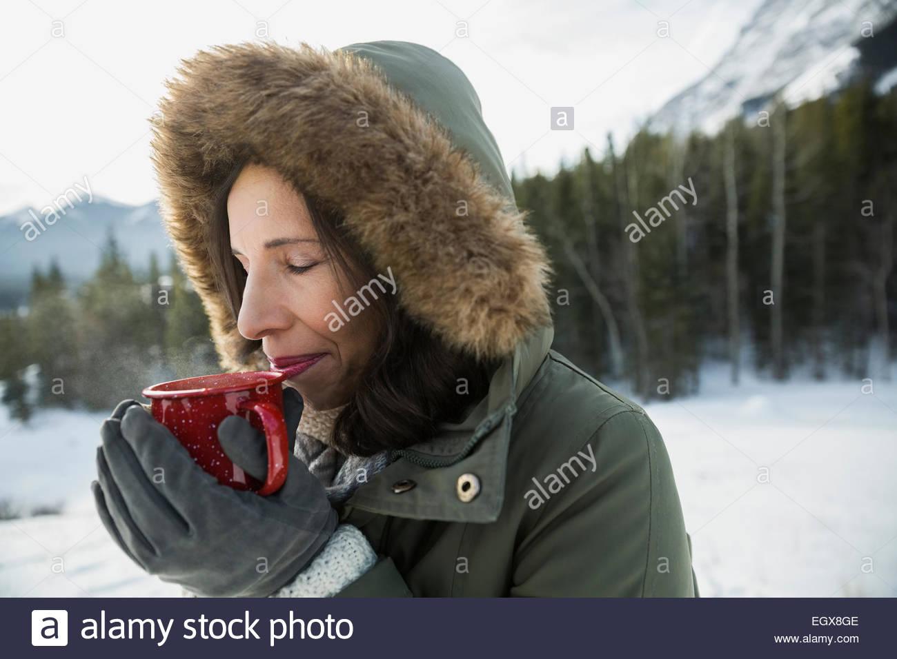 Femme au fur hood bénéficiant du chocolat chaud à l'extérieur Photo Stock