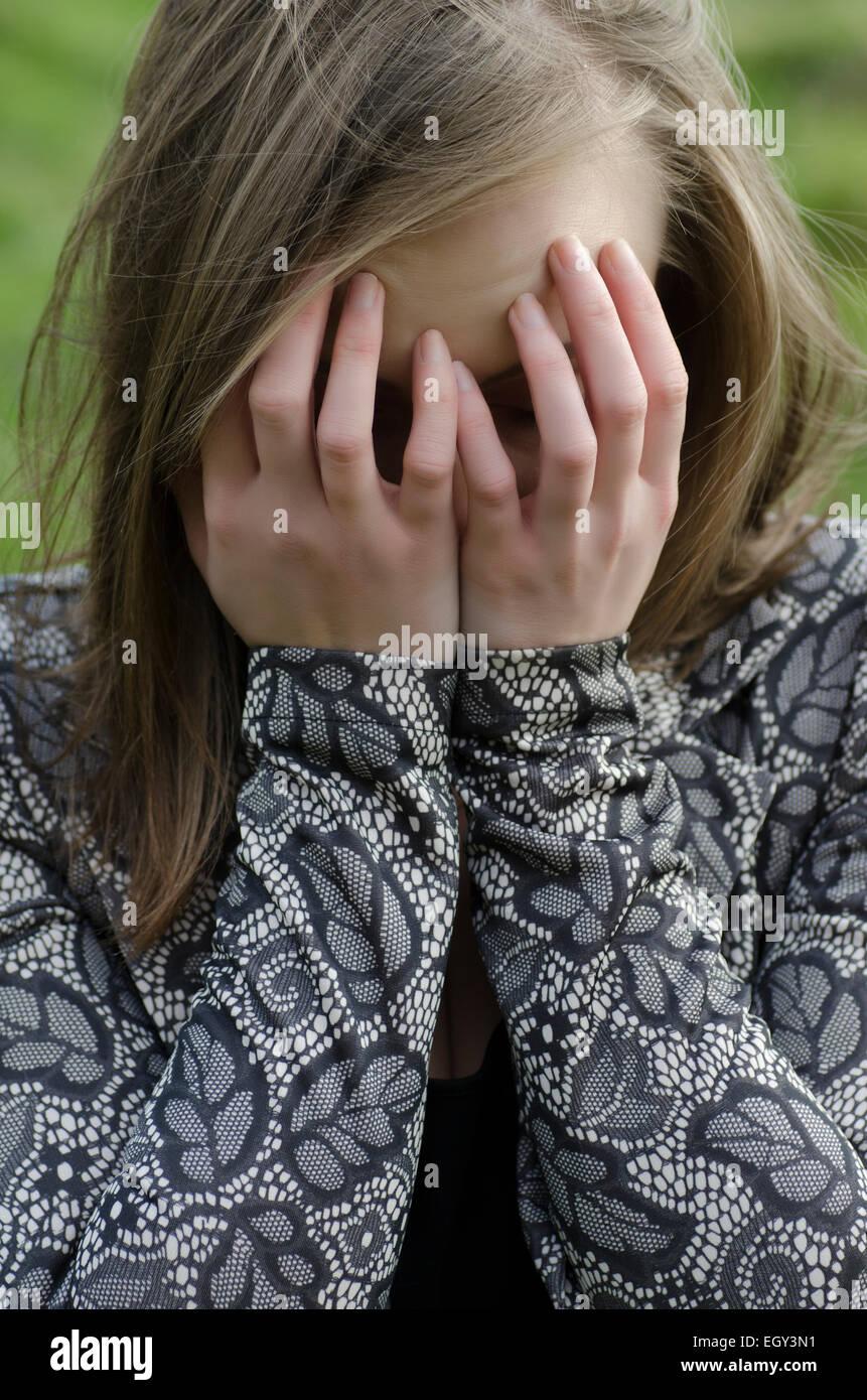 Jeune femme la tête dans les mains de pleurer à l'extérieur Photo Stock