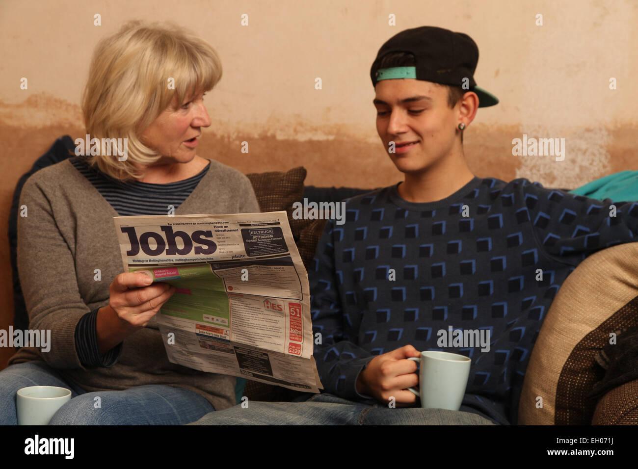 Adolescent avec grand-mère à la recherche d'emploi - journal à parution du modèle Photo Stock