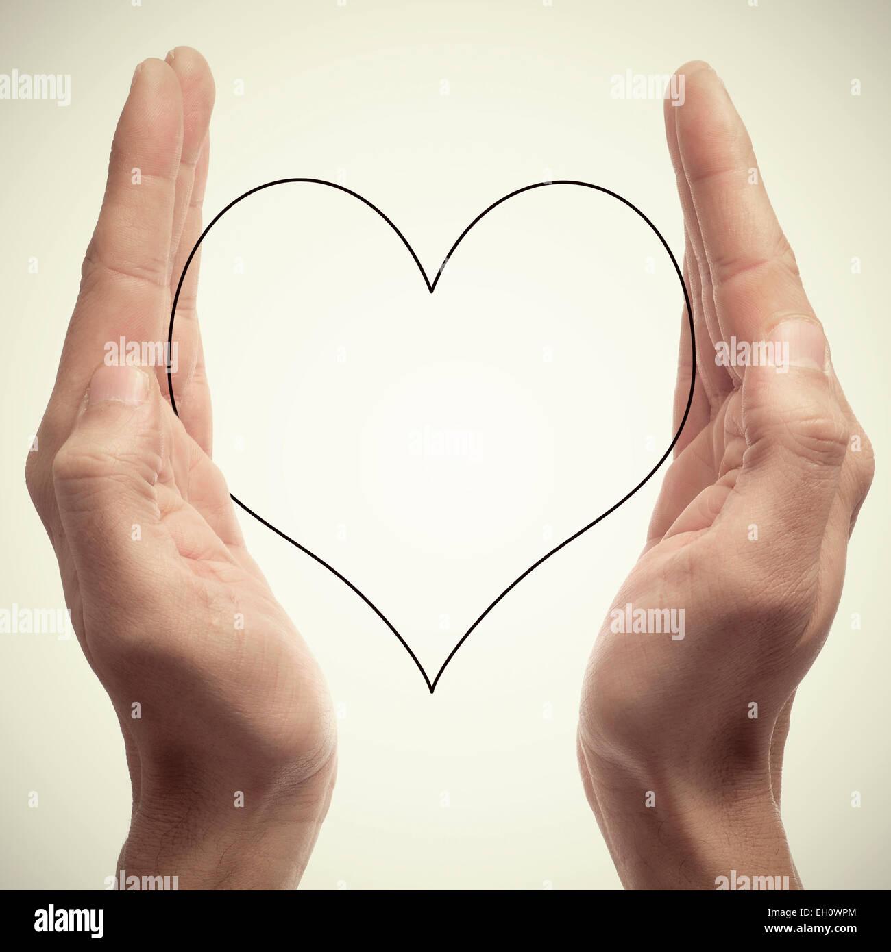 Les mains de l'homme tenant une silhouette d'un cœur, avec un effet rétro Photo Stock
