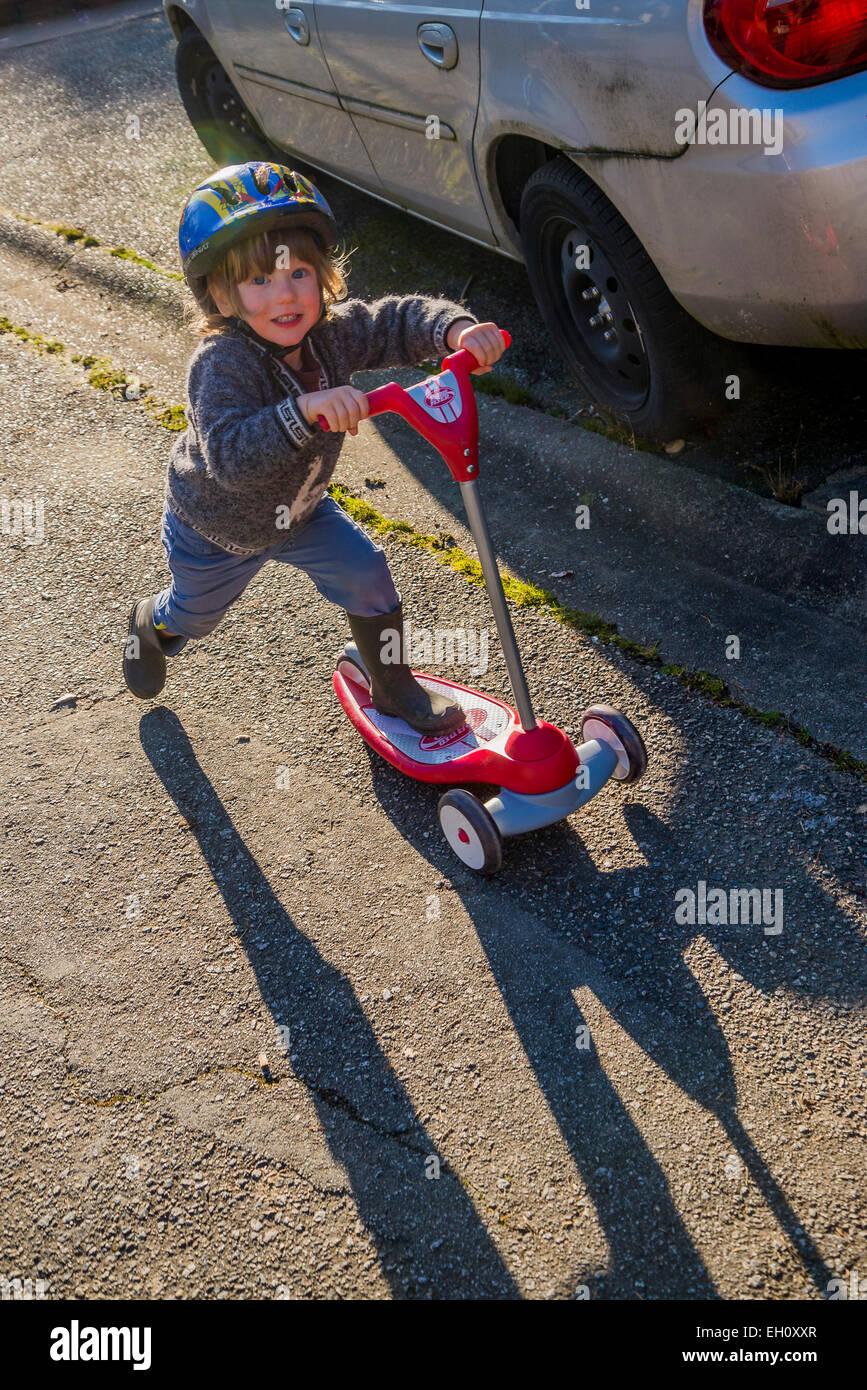 Jeune garçon sur un scooter jouet. Photo Stock