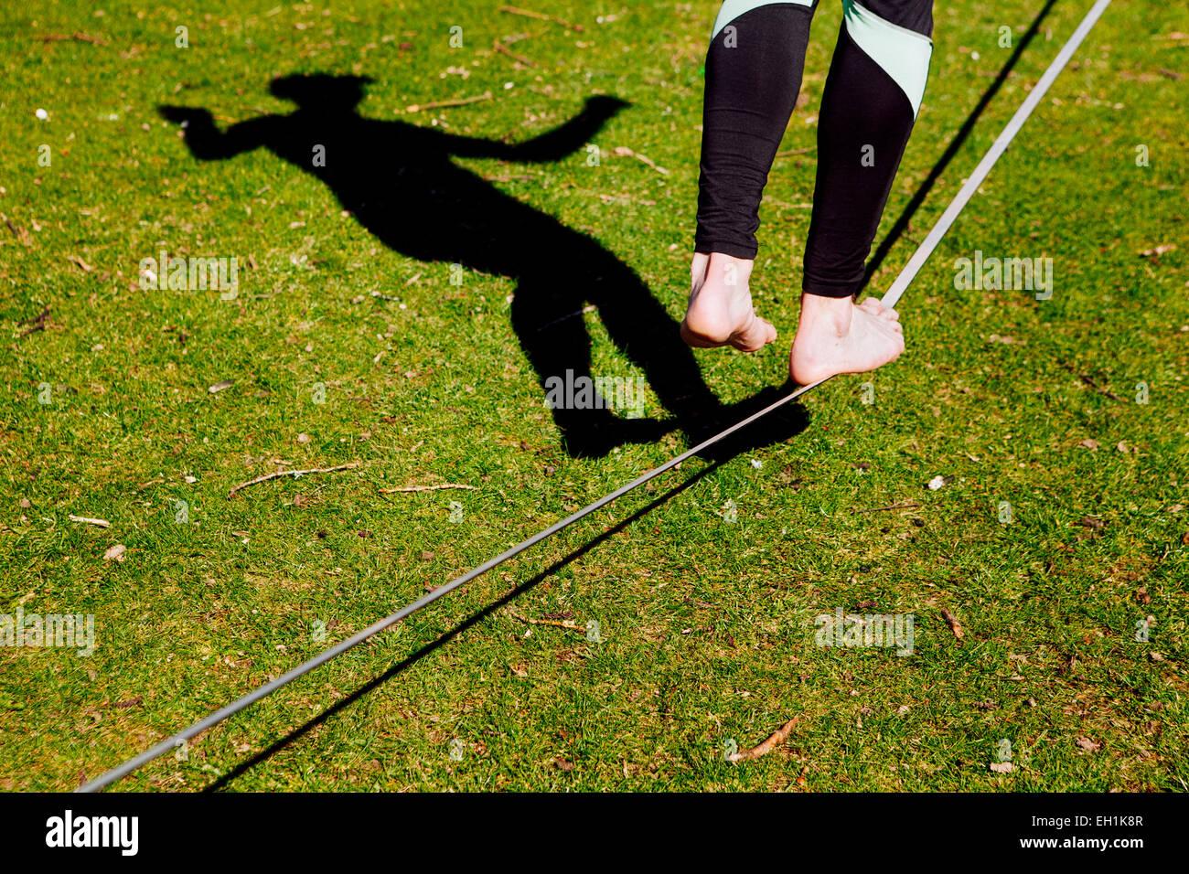 La section basse de l'homme en équilibre sur Slack-line in park Photo Stock