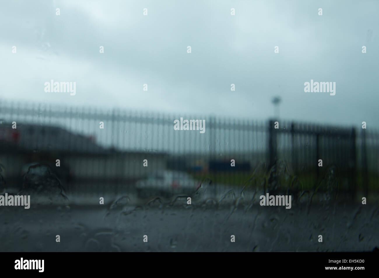 Triste image floue d'un parking et haute clôture d'une balle dans la fenêtre d'une voiture Photo Stock