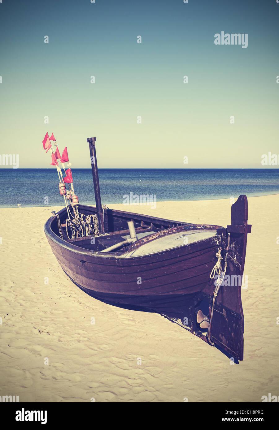 Retro photo filtrée de bateau de pêche sur la plage. Photo Stock