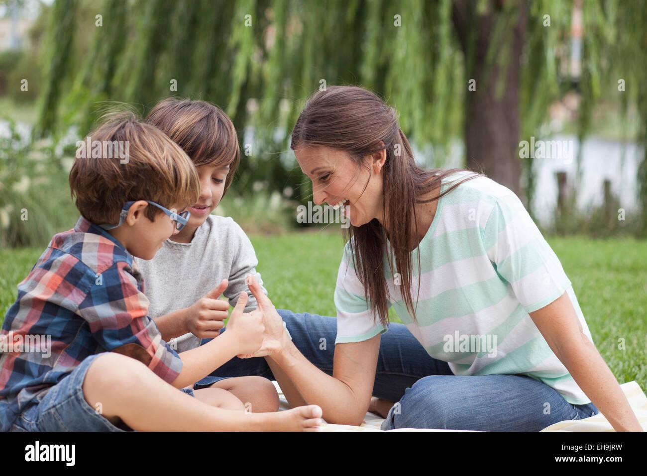 L'enseignement de mère ses fils comment terrasser le pouce Photo Stock